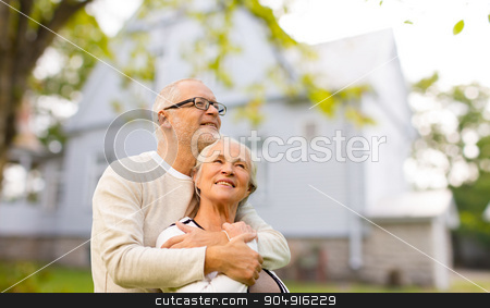 senior couple hugging over living house background stock photo, family, age, home, real estate and people concept - happy senior couple hugging over living house background by Syda Productions