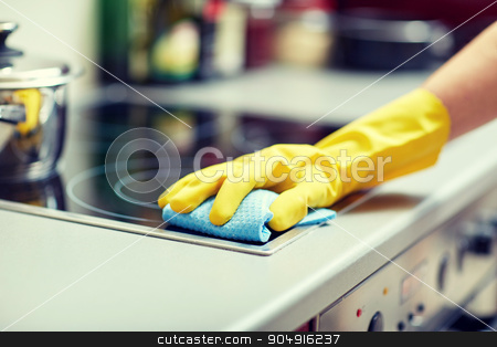 close up of woman cleaning cooker at home kitchen stock photo, people, housework and housekeeping concept - close up of woman hand in protective glove with rag cleaning cooker at home kitchen by Syda Productions