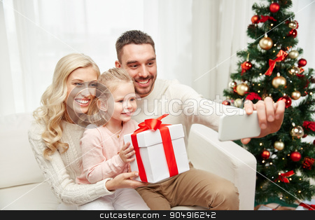 family taking selfie with smartphone at christmas stock photo, christmas, holidays, technology and people concept - happy family sitting on sofa and taking selfie picture with smartphone at home by Syda Productions