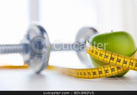 close up of dumbbell and apple with measuring tape stock photo, sport, fitness, diet and objects concept - close up of dumbbell and green apple with measuring tape by Syda Productions