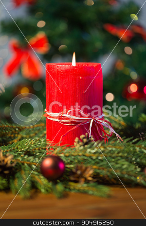 fir branch wreath with candle on wooden table stock photo, christmas, decoration, holidays and advertisement concept - close up of natural green fir branch wreath with red burning candle on wooden board by Syda Productions