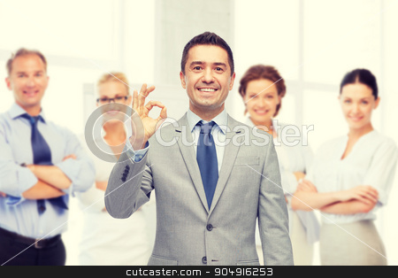 happy businessman in suit showing ok hand sign stock photo, business, people, gesture and success concept - happy smiling businessman in suit with team over office room background showing ok hand sign by Syda Productions