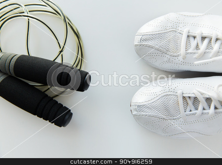 close up of sneakers and skipping rope stock photo, sport, fitness, healthy lifestyle, cardio training and objects concept - close up of sneakers and skipping rope by Syda Productions