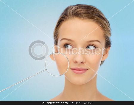 young woman face with magnifier showing good skin stock photo, beauty, people and health concept - smiling young woman face over blue background with magnifier showing perfect skin by Syda Productions