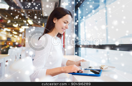 smiling woman with tablet pc and coffee at cafe stock photo, leisure, people, holidays, technology and lifestyle concept - smiling young woman with tablet pc computer drinking coffee at cafe over snow effect by Syda Productions