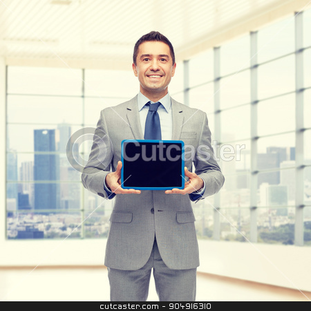happy businessman in suit showing tablet pc screen stock photo, business, people and technology concept - happy smiling businessman in suit showing tablet pc computer black blank screen over city office room window background by Syda Productions
