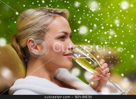 beautiful young woman drinking champagne at spa stock photo, people, beauty, lifestyle, holidays and relaxation concept - beautiful young woman in white bath robe lying on chaise-longue and drinking champagne at spa with snow effect by Syda Productions