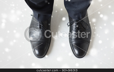 close up of man legs in elegant shoes with laces stock photo, people, business, fashion and footwear concept - close up of man legs in elegant shoes with laces or lace boots over snow effect by Syda Productions