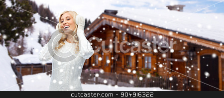 smiling young woman in winter earmuffs outdoors stock photo, winter, fashion, vacation, christmas and people concept - smiling young woman in earmuffs and sweater over wooden country house and snow background by Syda Productions