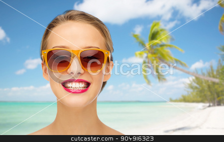 happy young woman in sunglasses with pink lipstick stock photo, people, accessory, summer vacation, travel and fashion concept - smiling young woman in sunglasses with pink lipstick on lips over tropical beach with palm background by Syda Productions
