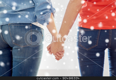 close up of lesbian couple holding hands stock photo, people, homosexuality, same-sex marriage, gay and love concept - close up of happy lesbian couple holding hands over snow effect by Syda Productions