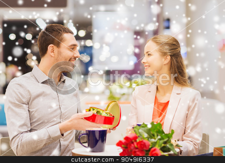 happy couple with chocolate box and roses in mall stock photo, love, romance, valentines day, couple and people concept - happy young couple with red flowers and open chocolate box in at cafe mall with snow effect by Syda Productions