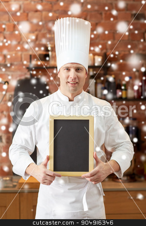 happy male chef with blank menu board in kitchen stock photo, cooking and people concept - happy male chef cook with black blank menu chalk board in kitchen in restaurant kitchen over snow effect by Syda Productions