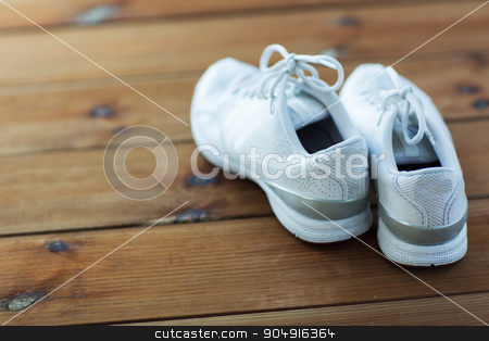 close up of sneakers on wooden floor stock photo, sport, fitness, shoes, footwear and objects concept - close up of sneakers on wooden floor by Syda Productions