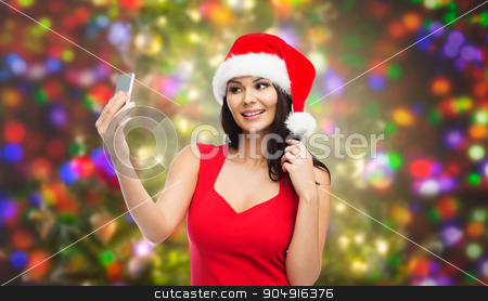 woman in santa hat taking selfie by smartphone stock photo, people, holidays, christmas and technology concept - beautiful sexy woman in red santa hat taking selfie picture by smartphone over party lights background by Syda Productions