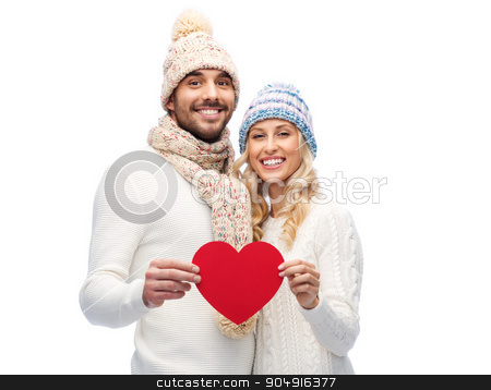 smiling couple in winter clothes with red heart stock photo, love, valentines day, couple, christmas and people concept - smiling man and woman in winter hats and scarf holding red paper heart shape by Syda Productions