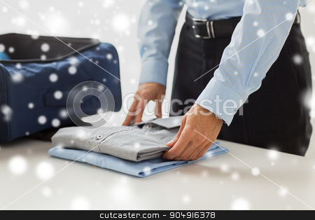 businessman packing clothes into travel bag stock photo, business, trip, luggage and people concept - close up of businessman packing clothes into travel bag over snow effect by Syda Productions