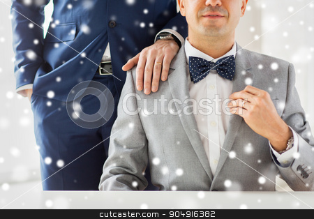 close up of male gay couple with wedding rings on stock photo, people, celebration, homosexuality, same-sex marriage and love concept - close up of male gay couple with wedding rings on putting hand on shoulder over snow effect by Syda Productions