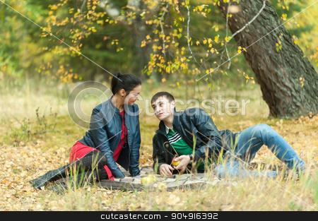 Young romantic couple sits on plaid. Autumn picnic stock photo, Young attractive man and girl sit on plaid. Autumn picnic rest on nature by Aikon