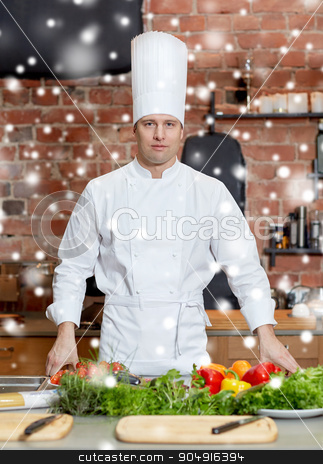 happy male chef cook with vegetables in kitchen stock photo, cooking, food and people concept - happy male chef cook with vegetables on restaurant kitchen table over snow effect by Syda Productions
