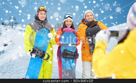 happy friends with snowboards and smartphone stock photo, winter sport, technology, leisure, friendship and people concept - happy friends with snowboards and smartphone taking picture over snow and mountain background by Syda Productions