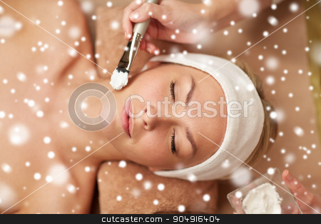woman face and beautician applying mask in spa stock photo, people, beauty, spa, cosmetology and skincare concept - close up of beautiful young woman lying with closed eyes and beautician hand applying facial mask by brush in spa salon with snow effect by Syda Productions