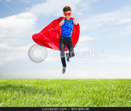 boy in super hero cape and mask showing thumbs up stock photo, imagination, gesture, childhood, movement and people concept - boy in red super hero cape and mask flying in air and showing thumbs up over blue sky and grass background by Syda Productions
