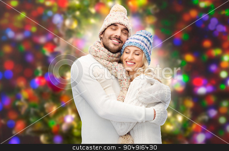 smiling couple in winter clothes hugging stock photo, winter, fashion, couple, christmas and people concept - smiling man and woman in hats and scarf hugging over lights background by Syda Productions