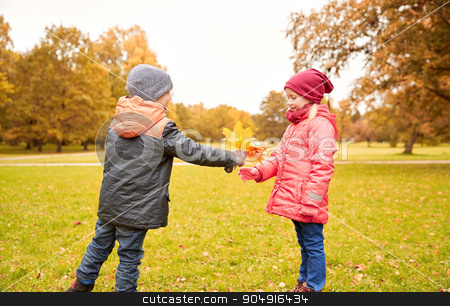 little boy giving autumn maple leaves to girl stock photo, childhood, leisure, friendship and people concept - happy little boy giving maple leaves to girl in autumn park by Syda Productions