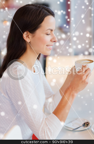 smiling young woman drinking coffee at cafe stock photo, drinks, people, holidays and lifestyle concept - smiling young woman drinking coffee at cafe over snow effect by Syda Productions