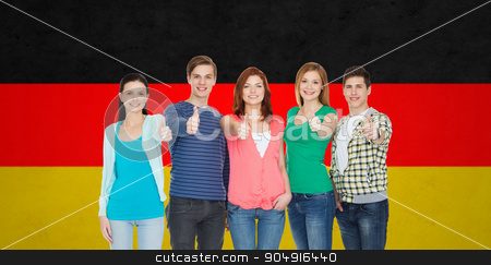 group of smiling students showing thumbs up stock photo, education, nationality, gesture and people concept - group of smiling friends or students standing and showing thumbs up over german flag background by Syda Productions