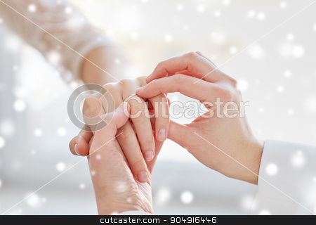close up of lesbian couple hands with wedding ring stock photo, people, homosexuality, same-sex marriage and love concept - close up of happy lesbian couple hands putting on wedding ring over snow effect by Syda Productions