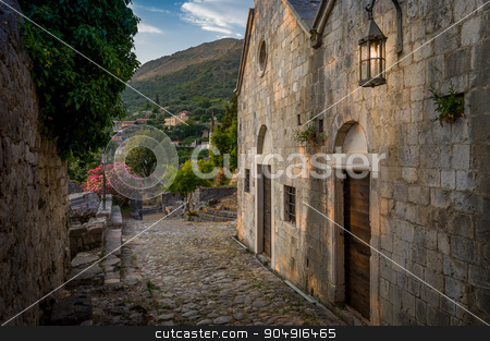Old Stari Bar fortress medieval buildings street stock photo, Old Stari Bar town fortress medieval street with church buildings at evening sunset and wall lantern lights. Bar, Montenegro by Alexander Nikiforov