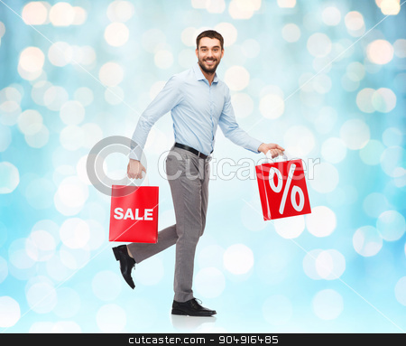 smiling man walking with red shopping bag stock photo, people, sale, discount and christmas concept - smiling man walking with red shopping bags over blue holidays lights background by Syda Productions