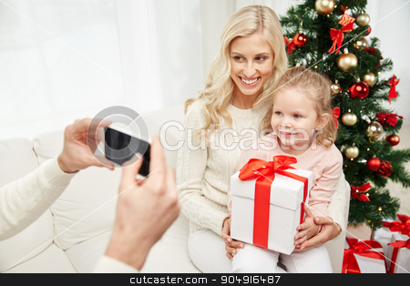 family taking picture with smartphone at christmas stock photo, christmas, holidays, technology and people concept - happy family sitting on sofa and taking picture with smartphone at home by Syda Productions