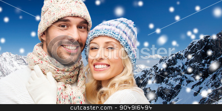 smiling couple in winter clothes over mountains stock photo, winter, fashion, couple, christmas and people concept - smiling man and woman in hats and scarf hugging over snow and mountains background by Syda Productions