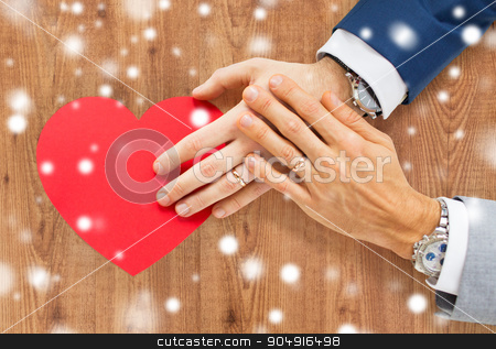 close up of male gay couple hands with red heart stock photo, people, homosexuality, same-sex marriage, valentines day and love concept - close up of happy married male gay couple hands with red paper heart shape over wooden background and snow effect by Syda Productions