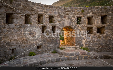 Medieval fortress wall and gate stock photo, Medieval fortress wall and sunset sunlight coming through the arch gate. Old Bar fortress, Montenegro by Alexander Nikiforov