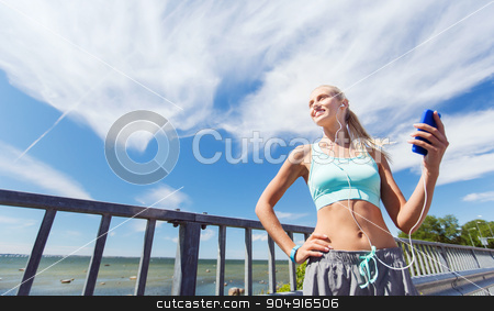 happy woman with smartphone and earphones outdoors stock photo, fitness, sport, people, technology and healthy lifestyle concept - smiling young woman with smartphone and earphones listening to music and exercising outdoors by Syda Productions