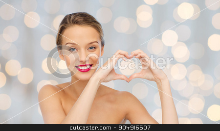 smiling young woman showing heart shape hand sign stock photo, beauty, people, love, valentines day and make up concept - smiling young woman with pink lipstick on lips showing heart shape hand sign over holidays lights background by Syda Productions