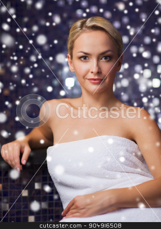 beautiful woman sitting in bath towel at sauna stock photo, people, beauty, spa, healthy lifestyle and relaxation concept - beautiful young woman sitting in bath towel at sauna with snow effect by Syda Productions
