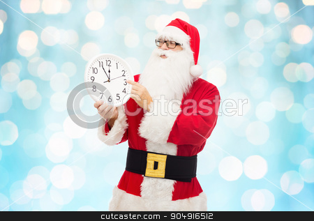 man in costume of santa claus with clock stock photo, christmas, holidays, time and people concept - man in costume of santa claus with clock showing twelve pointing finger over blue holidays lights background by Syda Productions