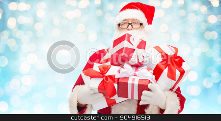 man in costume of santa claus with gift boxes stock photo, christmas, holidays and people concept - man in costume of santa claus with gift boxes over blue holidays lights background by Syda Productions