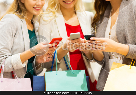 happy women with smartphones and shopping bags stock photo, sale, consumerism, technology and people concept - happy young women with smartphones and shopping bags talking in mall by Syda Productions