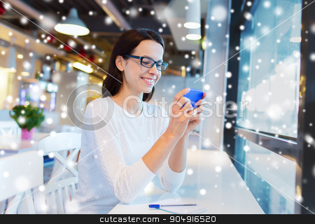 smiling woman with smartphone at cafe stock photo, business, people, technology and lifestyle concept - smiling young woman in eyeglasses texting message with smartphone at cafe over snow effect by Syda Productions