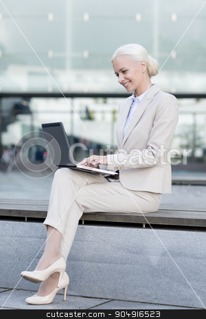 smiling businesswoman working with laptop outdoors stock photo, business, education, technology and people concept - smiling businesswoman working with laptop computer on city street by Syda Productions