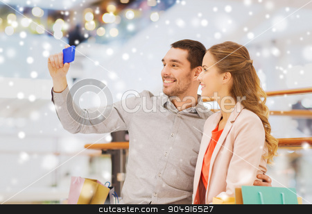 happy couple with smartphone taking selfie in mall stock photo, sale, consumerism, technology and people concept - happy young couple with shopping bags and smartphone taking selfie in mall with snow effect by Syda Productions