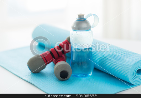 close up of bottle, dumbbells and sports mat stock photo, sport, fitness, healthy lifestyle and objects concept - close up of bottle with water, dumbbells and sports mat by Syda Productions