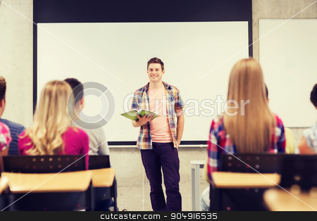 group of smiling students in classroom stock photo, education, high school, teamwork and people concept - smiling student boy with notebook standing in front of students in classroom by Syda Productions