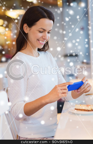 smiling woman with smartphone and coffee at cafe stock photo, drinks, food, people, technology and lifestyle concept - smiling young woman taking picture with smartphone and drinking coffee at cafe over snow effect by Syda Productions